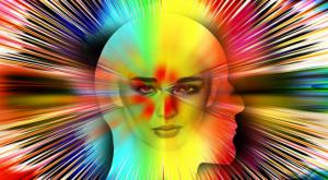 Representación de la consciencia a través de dos siluetas de una cara superpuestas entre rayos de colores.