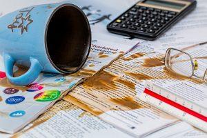 Taza de café manchando documentos de trabajo