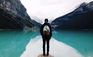 Excursionista contemplando un lago entre montañas