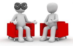 Dos personas hablando y una de ellas tiene espirales sobre los ojos