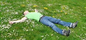 Hombre durmiendo tranquilo en un césped con flores.