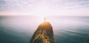Persona sobre un acantilado observando la puesta de sol