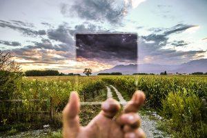 Una mano sosteniendo una imagen más clara del campo que tiene al fondo