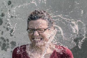Mujer sorprendida recibiendo agua en la cara