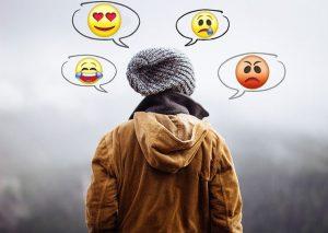 Persona con bocadillos de cómic sobre su cabeza en los que hay diferentes emojis: enamorado, triste, riendo y enfadado.