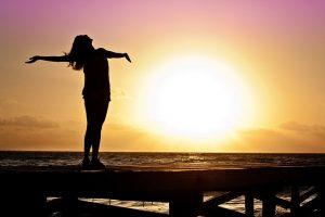 Mujer abriendo los brazos libremente y con confianza frente al sol en la playa