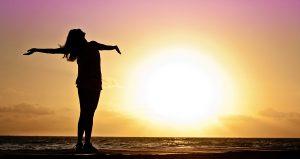 Mujer abriendo los brazos feliz frente a un sol poniente en la playa