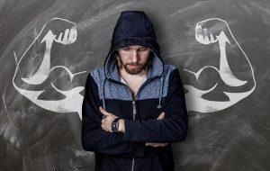 Deportista frente a una pizarra con brazos musculados pintados con tiza