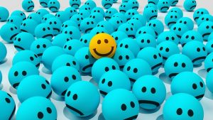 Cara sonriente entre un montón de caras tristes