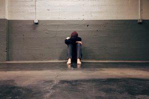 Joven sentado en el suelo con la cabeza gacha con actitud de tristeza y falta de motivación