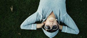 Joven tumbado relajadamente con los brazos en la nuca