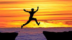 Persona saltando de la cima de una montaña a otra en actitud de motivación infinita