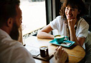 mujer sonriente mirando a un hombre mientras mantienen una conversación en una cafetería