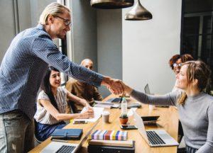 Hombre y mujer saludándose por primera vez en una reunión de trabajo