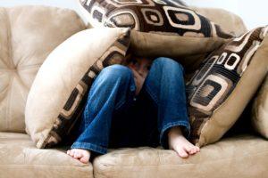 niño asustado tapándose con los cojines en un sillon