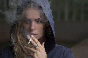 Mujer fumando con adicción al tabaco y quiere superarlo