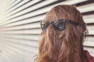 persona con pelo sobre la cara con gafas rayban siendo divertida